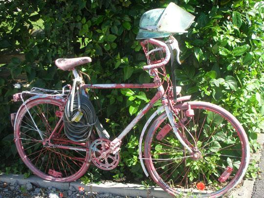 Ein altes Feuerwehrrad mit Helm, gesehen in Zienken am Rhein