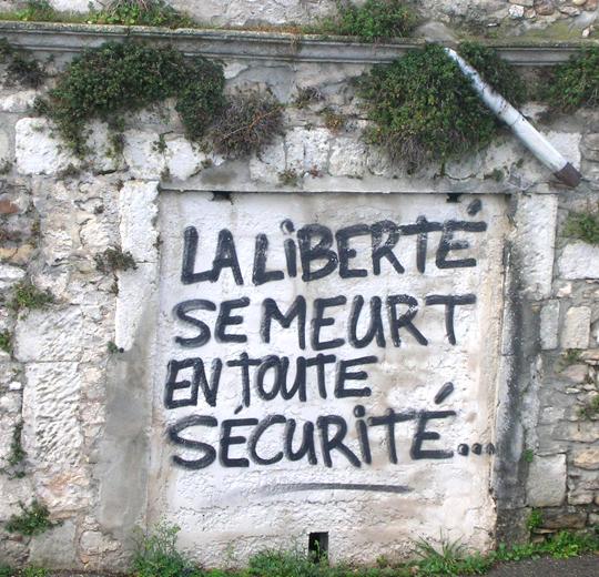 """An einer Mauer oberhalb der Rhone: """"Die Freiheit stirbt in totaler Sicherheit""""."""