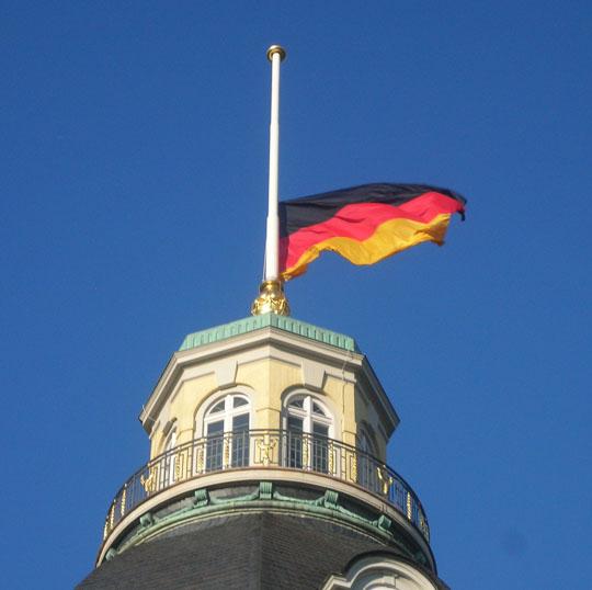 Blauer Himmel und eine deutsche Flagge auf Halbmast