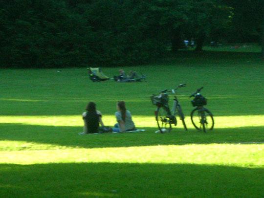Studentinnen mit Fahrrädern auf einer Wiese hinter dem Schloss