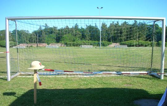 """Jenseits des """"Campingplatzes"""": das Fußballfeld. Links die Polizeimütze von Reidar"""