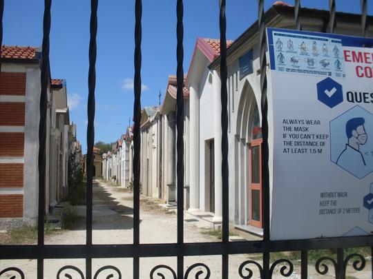 Corona-Warnung vor einem Friedhof
